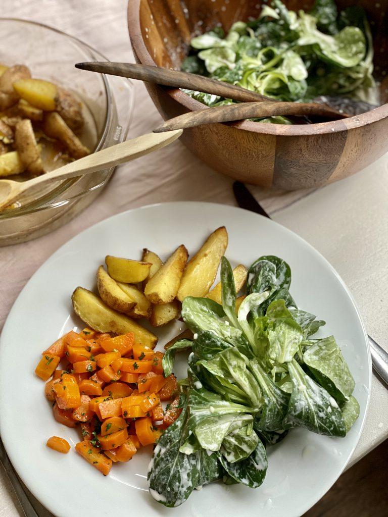 Winterlicher Feldsalat auf weißem Teller mit Ofenkartoffeln und Möhrengemüse
