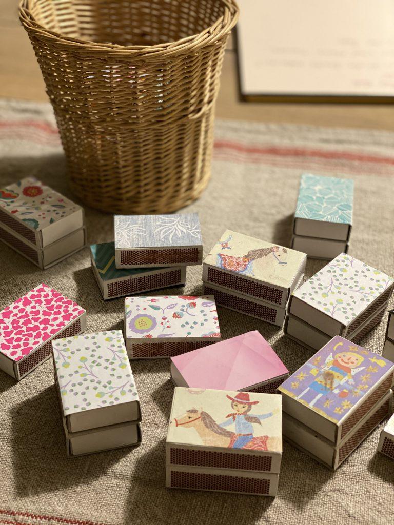 Streichholzschachteln mit schönem Papier beklebt, auf Leinentischdecke auf Holztisch
