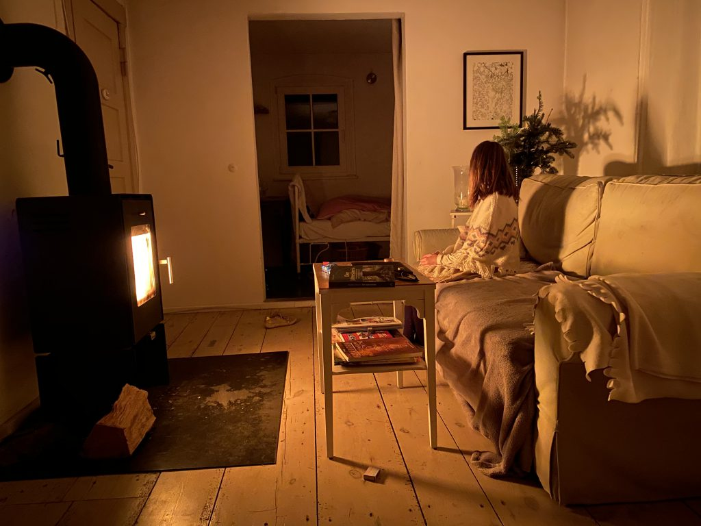 Zimmer mit Holzofen, nur durch das Feuer beleuchtet