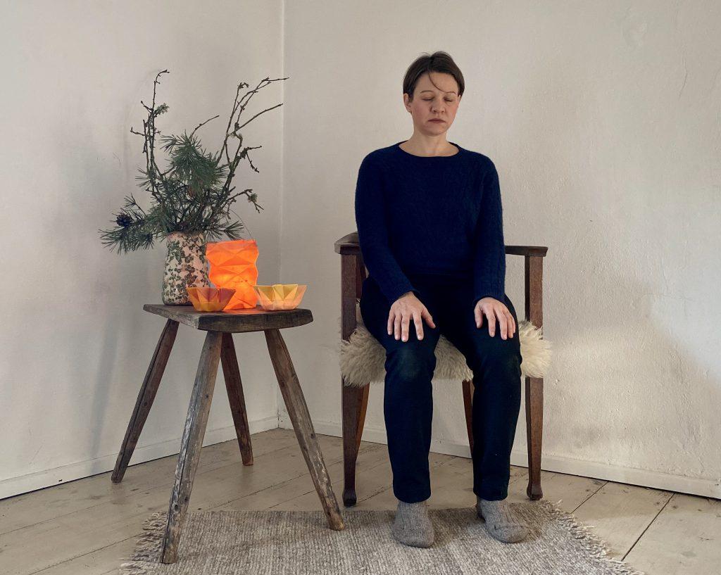 Ich auf Stuhl, Augen geschlossen und Hände auf den Knien beim Meditieren