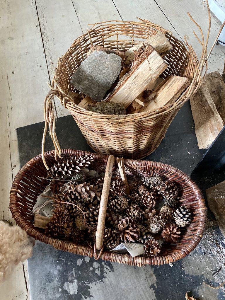 Zwei Körbe auf Holzboden, einer mit Tannenzapfen, der andere mit Anmachholz