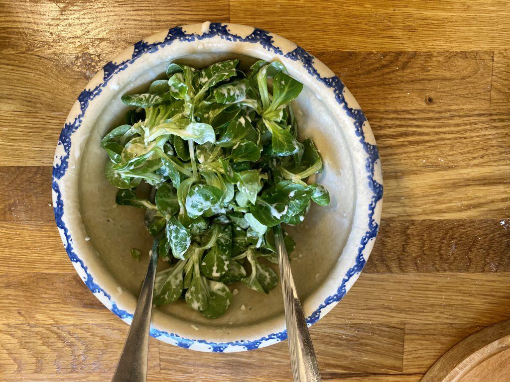 Winterlicher Feldsalat mit Sahnesauce in Salatschüssel von oben auf Holztisch