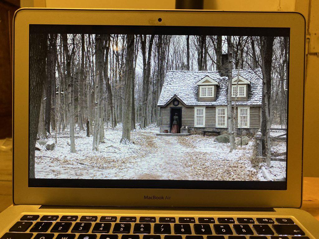 """Computerbildschirm mit Szene aus """"Anne with an E"""" (weiß beschneites Haus im Wald)"""