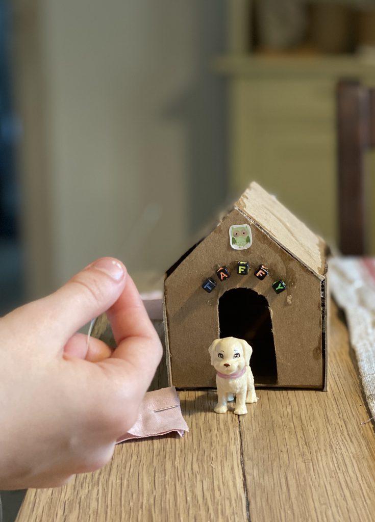 kleine Hundehütte aus Pappe auf Holztisch mit weißem Hündchen davor, Kinderhand mit Nähfaden und Stoff davor