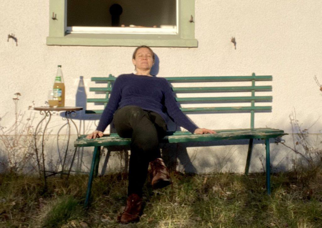 Ich sitze auf der Bank vor dem Haus und schaue mit geschlossenen Augen in die Sonne