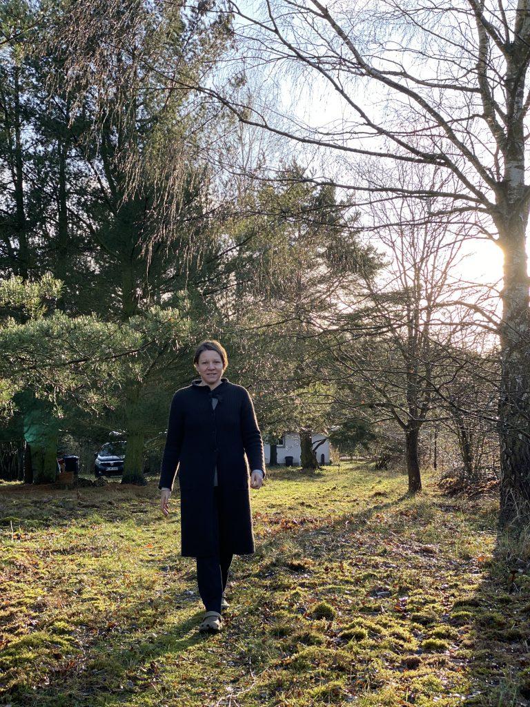 Frau mit schwarzer langer Jacke heget Weg in Garten entlang, von vorn zu sehen