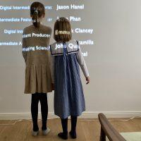 2 Kinder stehen vor Buchstaben an Wand von Filmprojektion