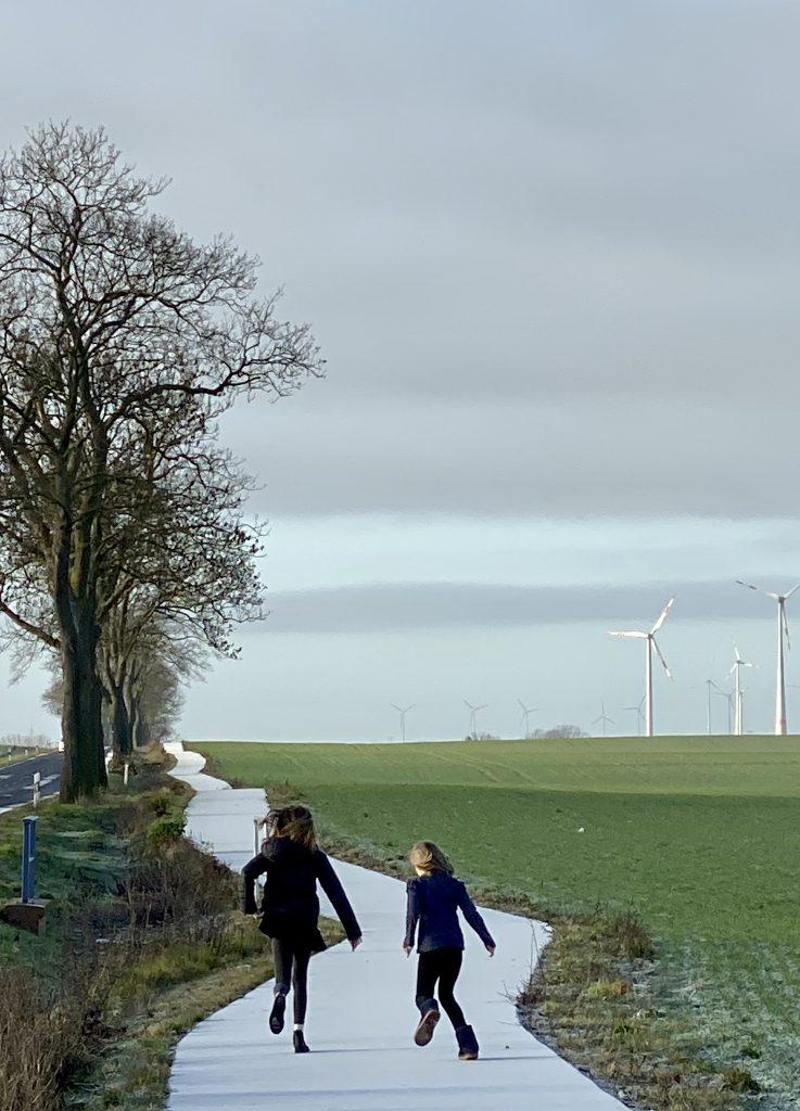 Zwei Kinder von hinten schlittern auf weißem schlängeligen Weg neben grünem Feld