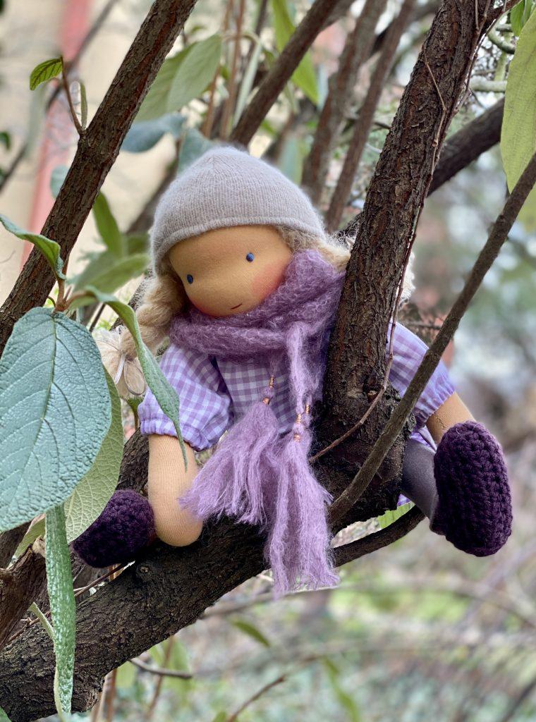 feinslieb Waldorfpuppe Livia, in Astgabel eines Baums sitzend