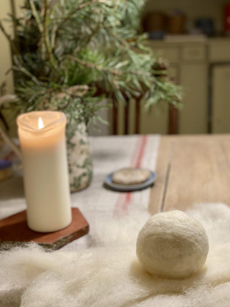 Wollkugel auf Holztisch vor weißer Kerze