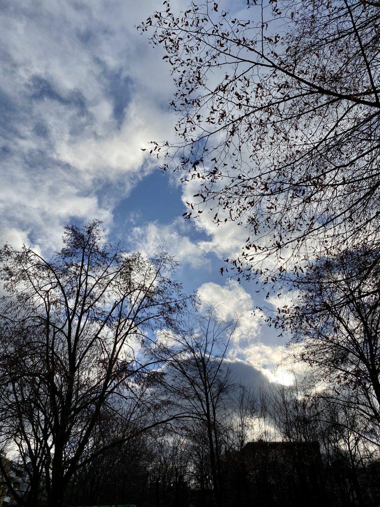 Winterhimmel über Stadtsilhouette, blauer Himmel mit Wolken im Gegenlicht