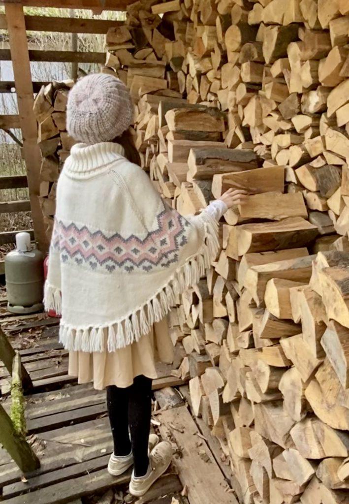 Kind vor Holzstapel greift nach Scheit.