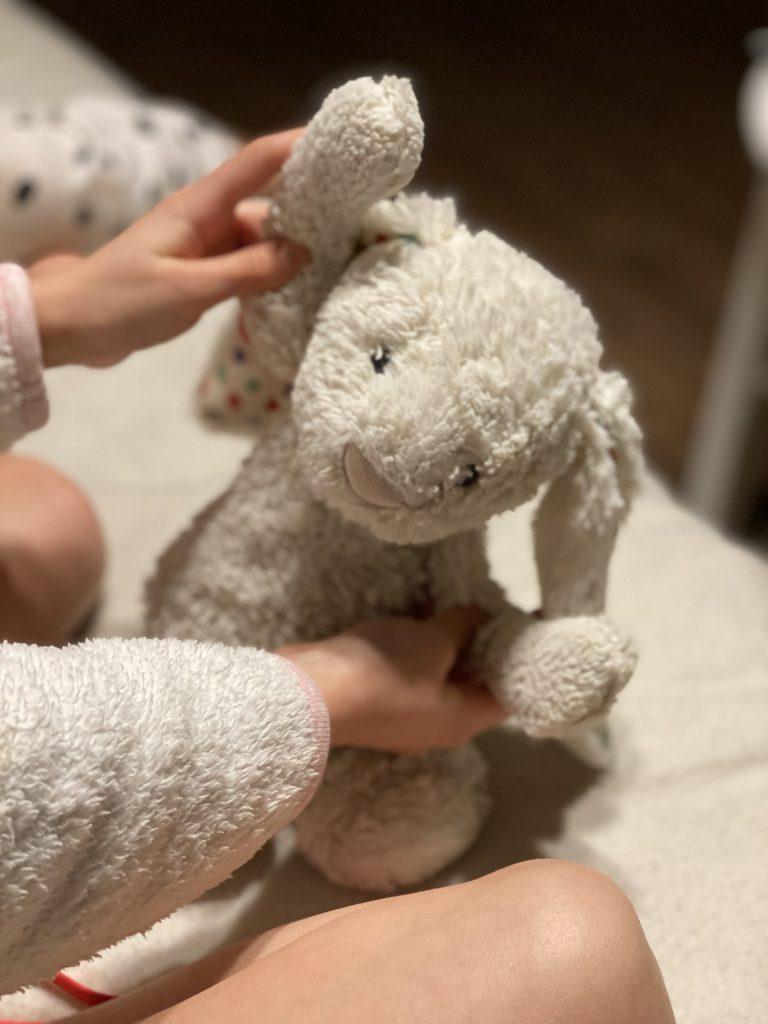 Grauer Plüschhase in Kinderhand