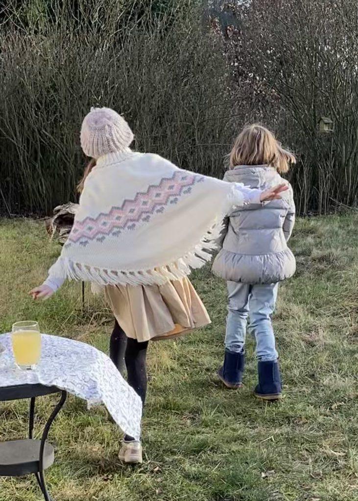 Zwei Kinder im winterlichen Garten (ohne Schnee)