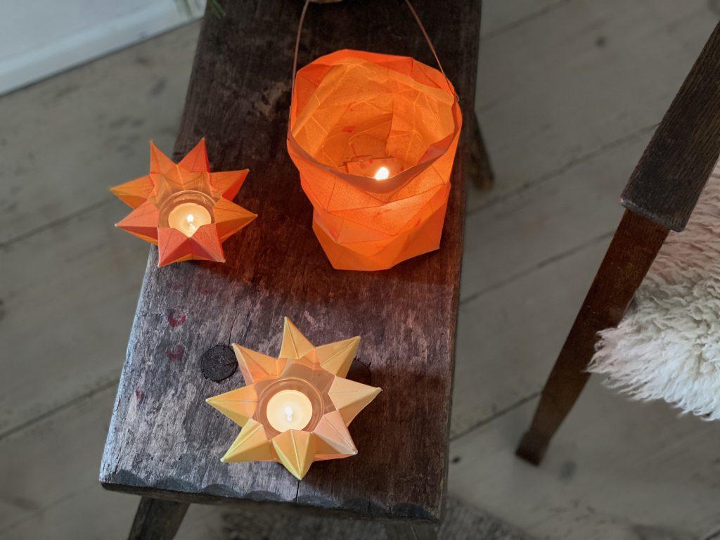 Drei gefaltete Sternenlichter bzw. Laternen auf Holzhocker