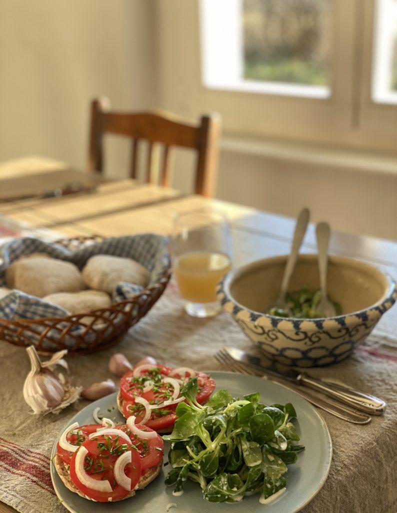 gedeckter Tisch mit Feldsalat, Tomatenbrötchen, Apfelsaft im Glas und Brötchenkorb
