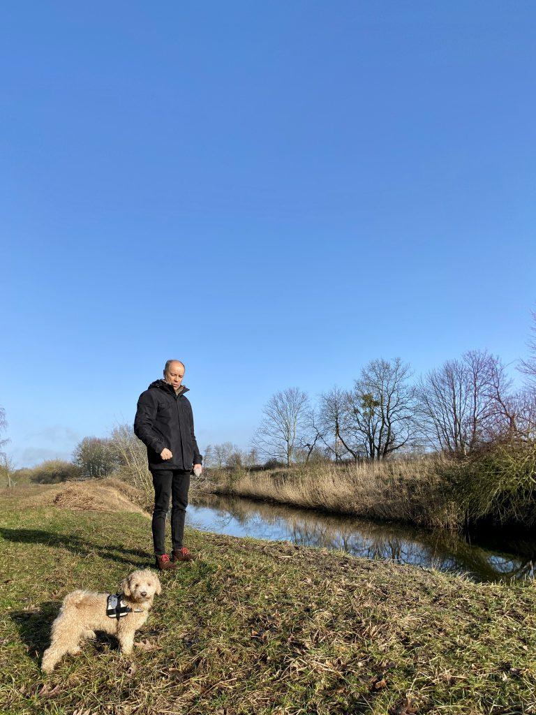 Mann und Hund an kleinem Fluss im Winter