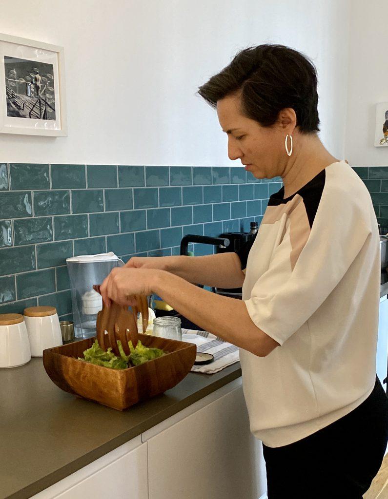 Frau macht Salat an mit hölzernem Salatbesteck