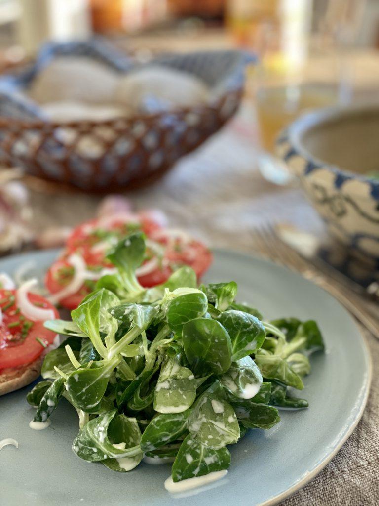 Gedeckter Tisch mit hellblauem Teller (nah), darauf Feldsalat und Tomatenbrötchen