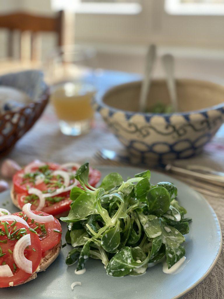 Feldsalat und Tomatenbrötchen auf Holztisch