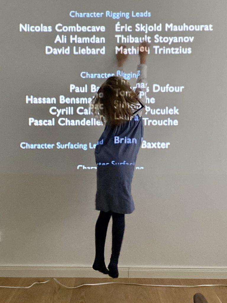 Kind versucht Buchstaben zu erhaschen an Wand von Filmprojektion