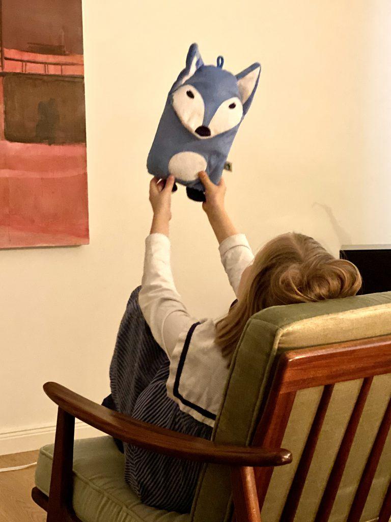 Kind in Midcentury-Sessel hält Wärmflaschen-Eule hoch