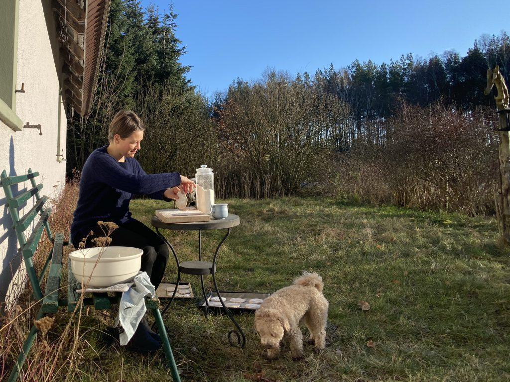 Ich beim Brötchenformen vor dem Haus, Welche mit Brötchen auf dem Grasboden und Hund auf der Wiese davor