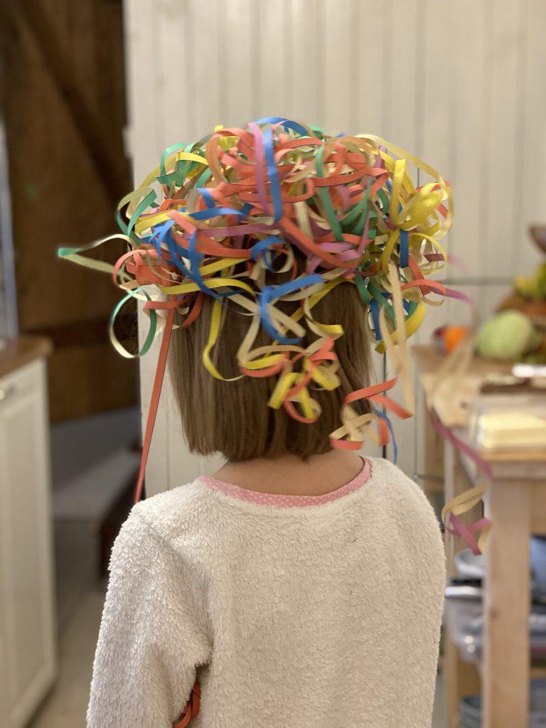 Mädchen von hinten mit Luftschlangen auf dem Kopf vor Holzwand in Küche