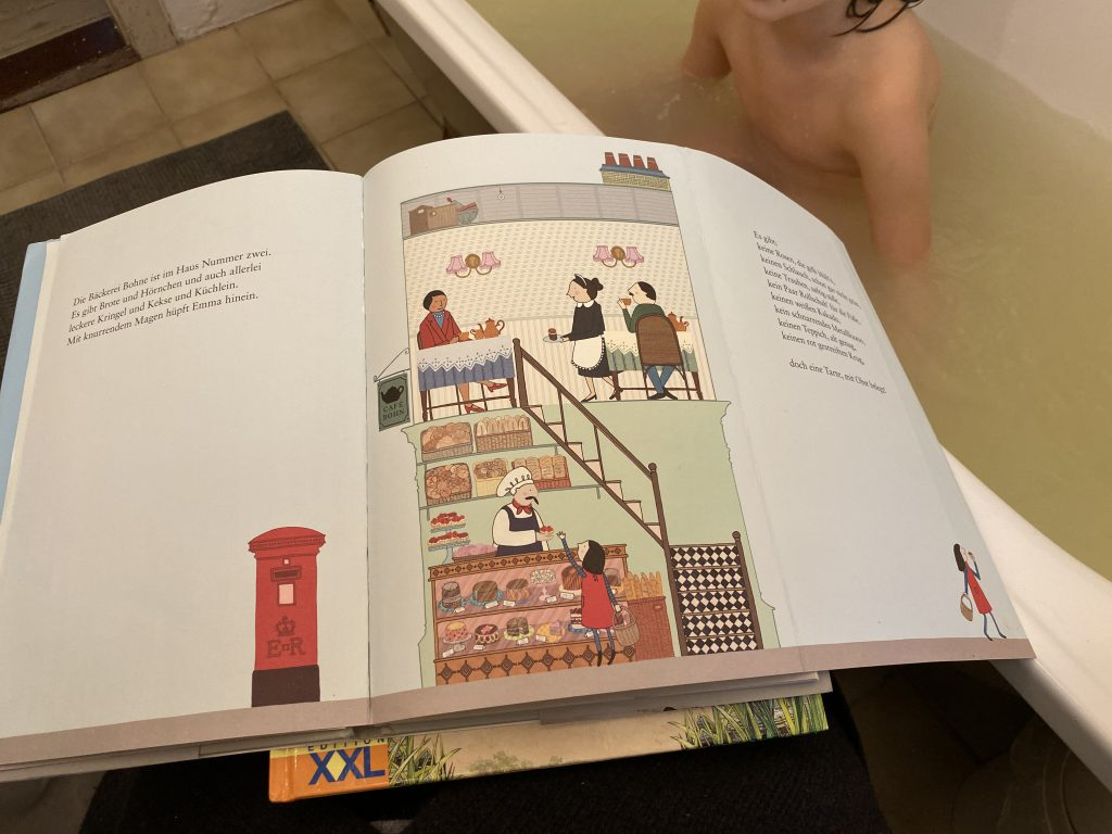 """aufgeschlagenes Kinderbuch """"Emma kauft ein"""" vor Badewanne"""