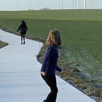 Zwei Kinder auf vereistem Weg neben grünem Feld
