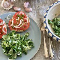 Gedeckter Tisch mit hellblauem teller, darauf Feldsalat und Tomatenbrötchen