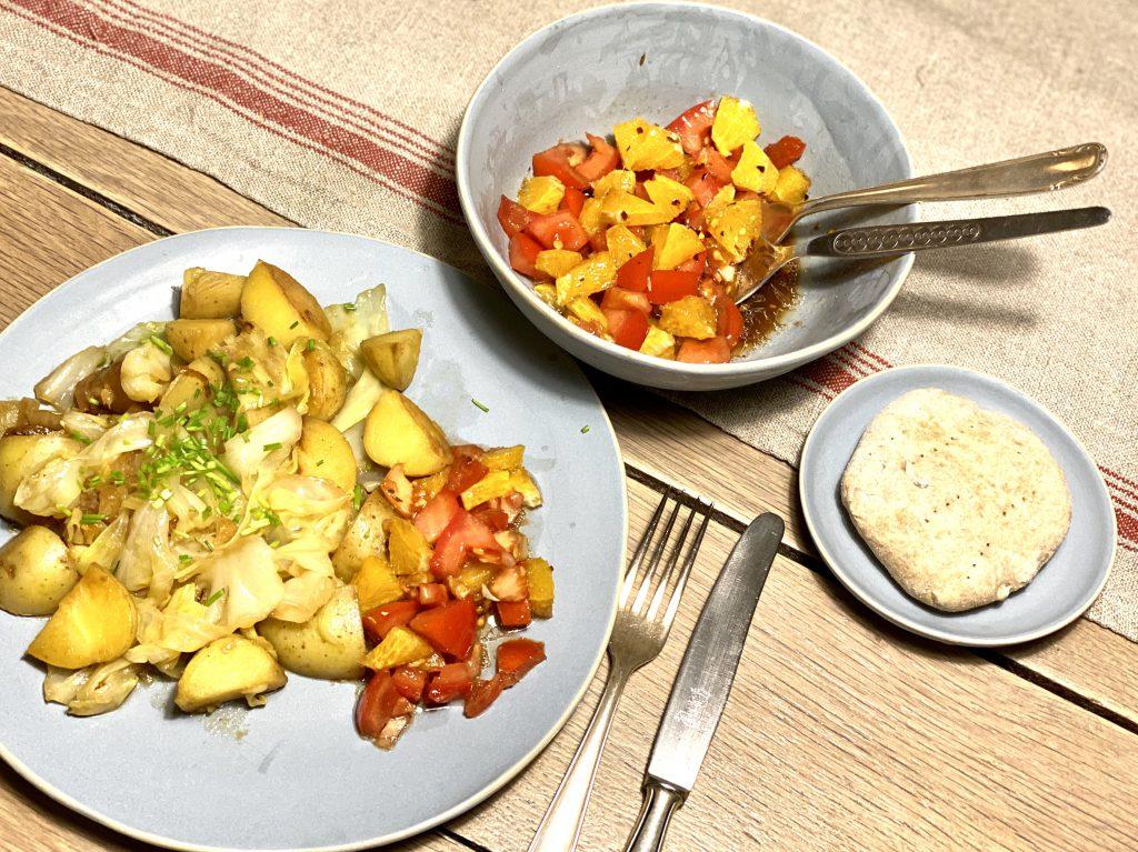 Teller mit Kartoffelpfanne und Tomaten-Orangensalat