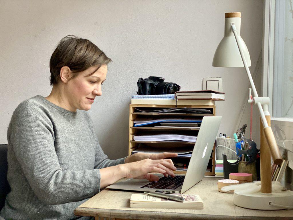 Maike am Schreibtisch, an der Tastatur des Laptops