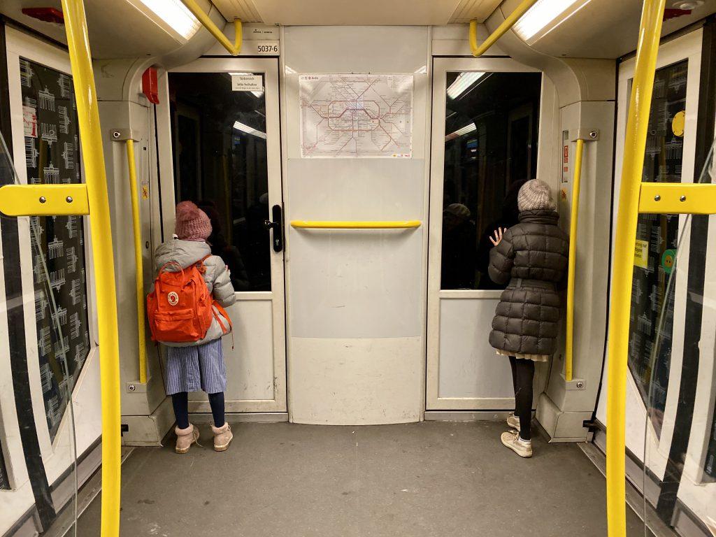 Zwei Kinder von hinten in der U-Bahn