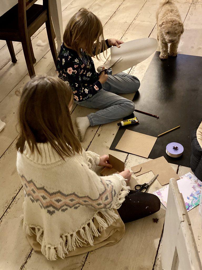 Kinder und Hund spielen auf Holzboden (Basteln)