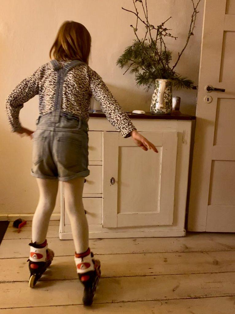 Kind fährt drinnen Inline vor weißer Holzkommode