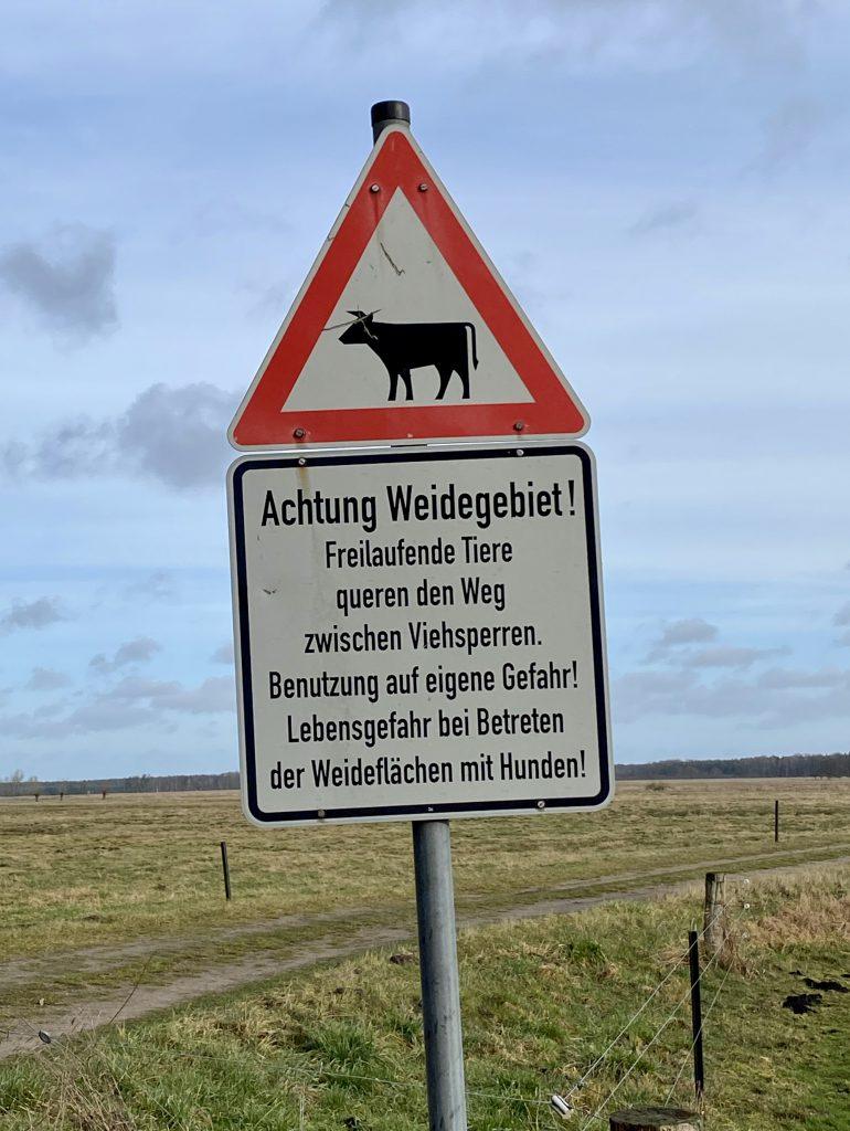 """Schild, das vor Weide davor warnt, das Weideland zu betreten: """"Lebensgefahr bei Betreten der Weideflächen mit Hunden"""""""