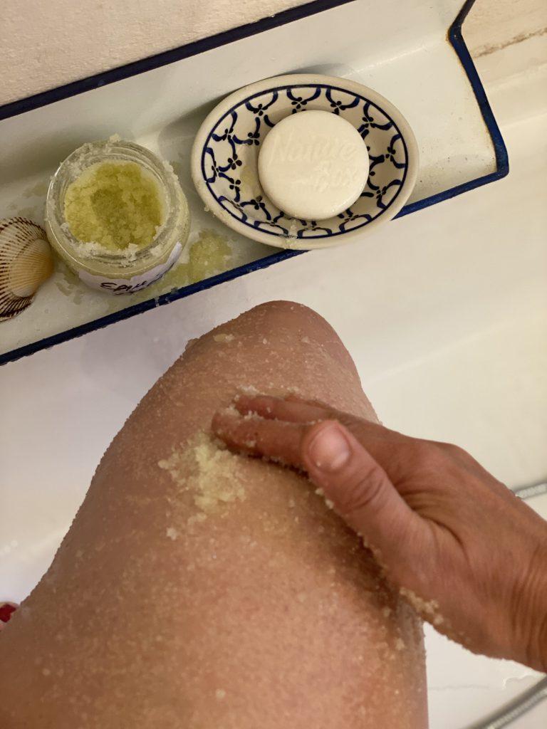 Efeu-Zucker-Peeling wird in der Wanne in den Oberschenkel einmassiert