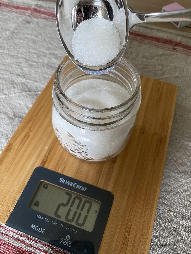 Zucker wird auf Waage in Schraubglas gegeben, Waage zeigt 200g an