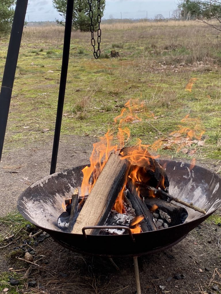 Feuer in großer feuerschale vor großer Wiese