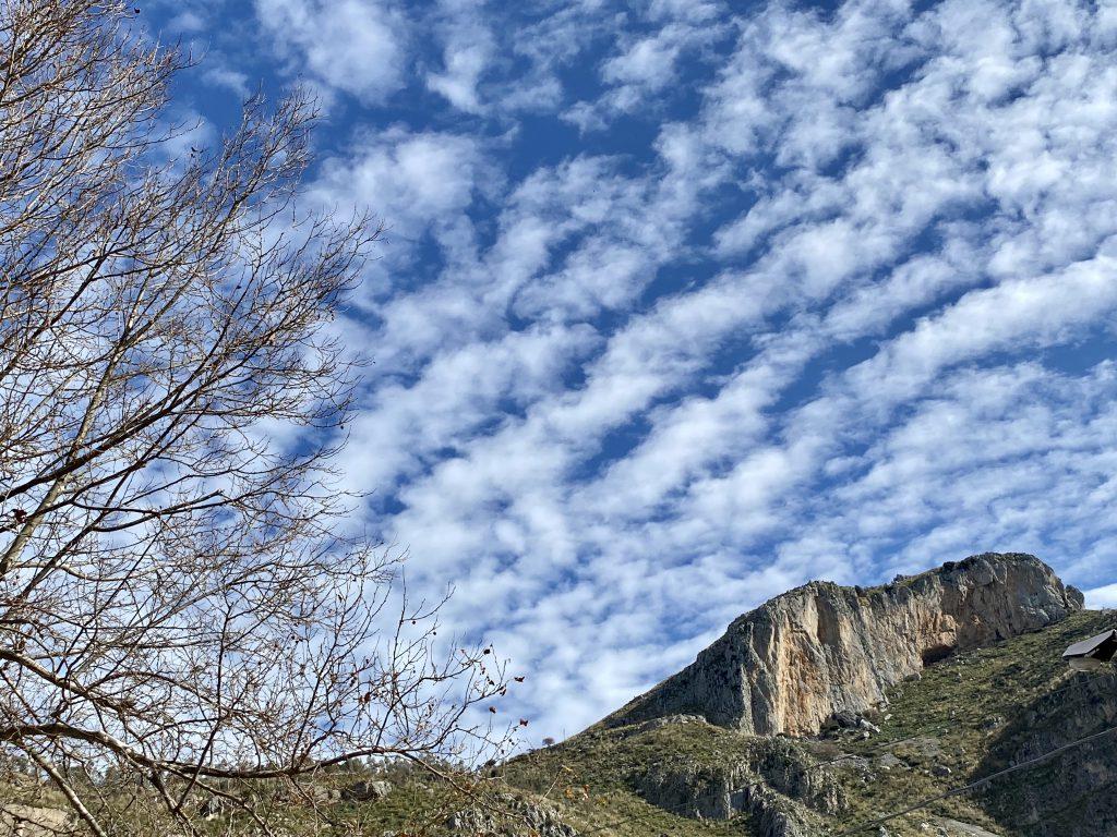 Wolkenstreifen vor blauem Himmel mit Felsen und Baum