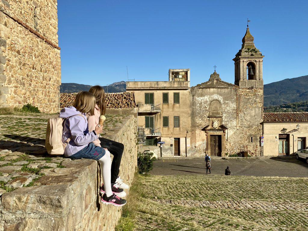 Kinder auf Mauer in Burghof mit blauem Himmel