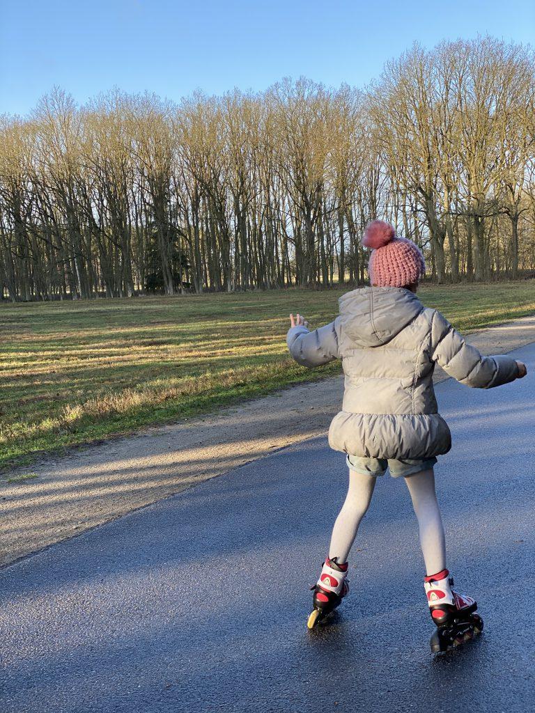 Kind fährt auf Straße in Natur Inliner