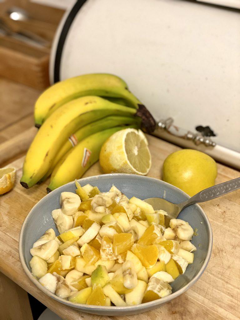Schüssel mit Obstsalat mit Obst dahinter