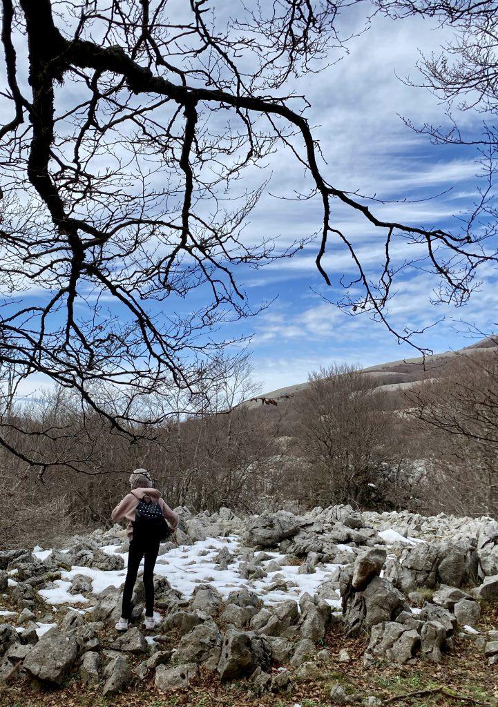 Kind von hinten auf Hügel mit Schneeresten