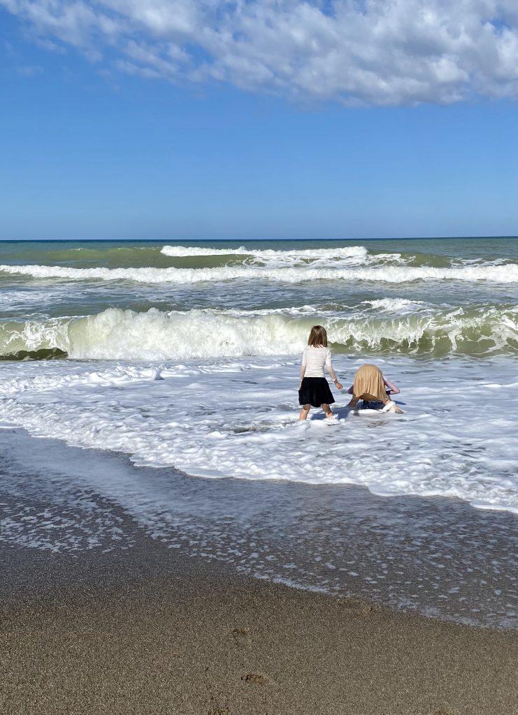 2 Kinder hocken im Wellensaum mit Kleidern an
