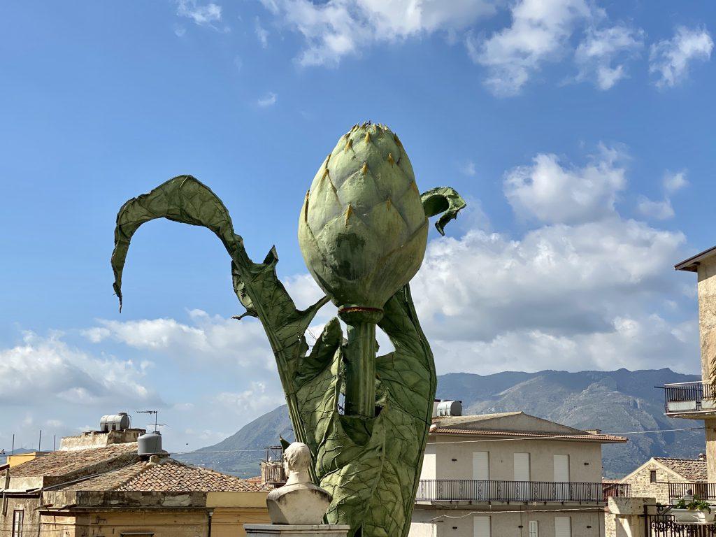 Artischocken-Skulptur vor blauem Himmel