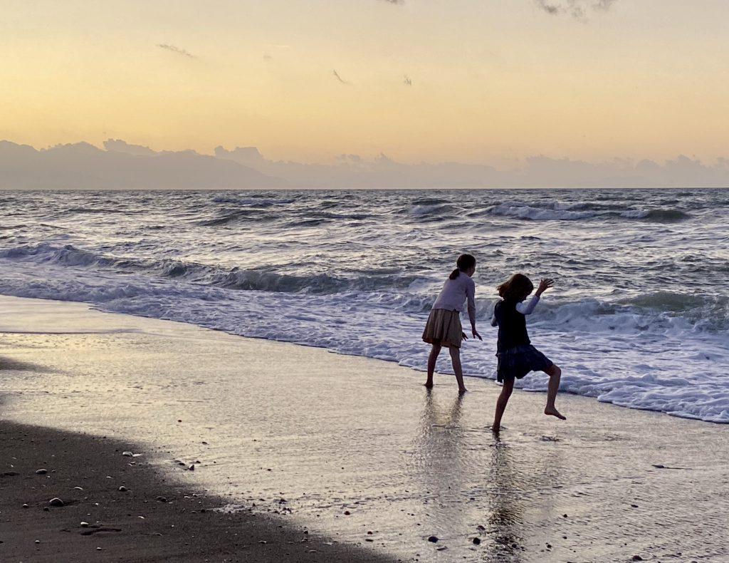 2 Kinder toben am Wasser vor rauschenden Wellen