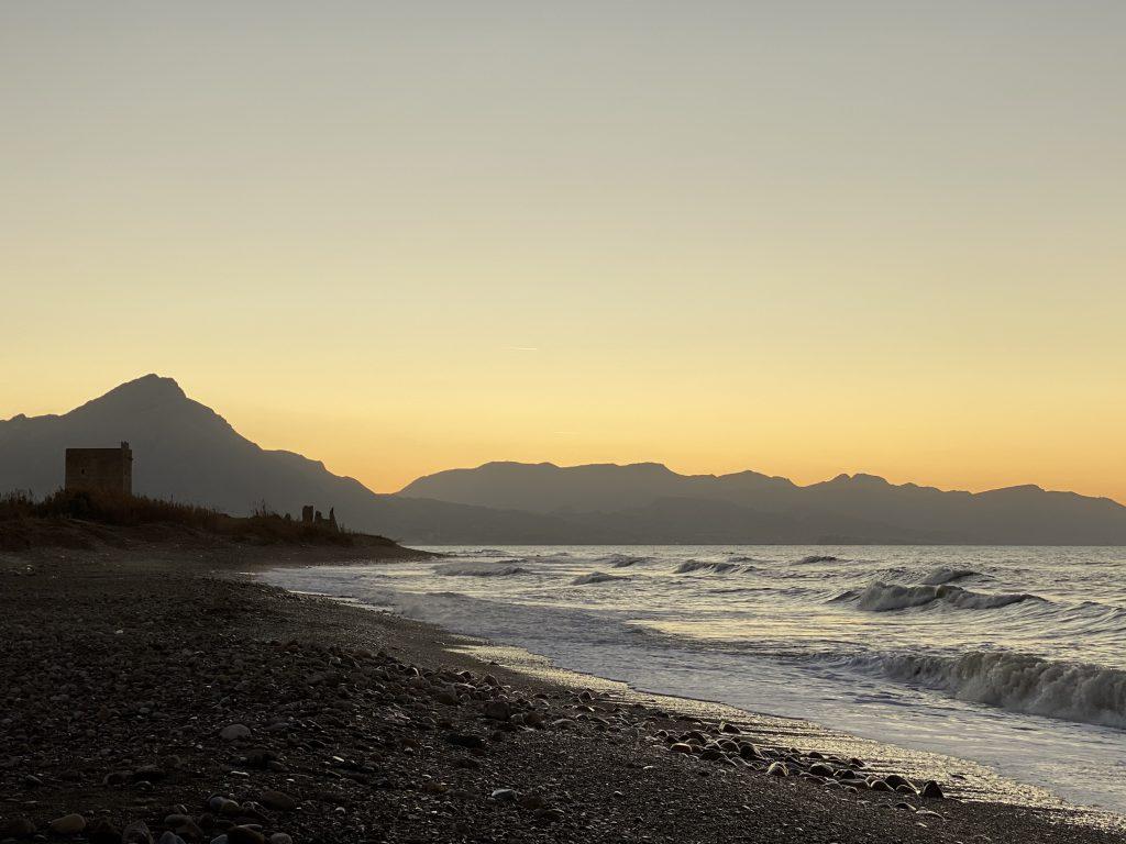 Küste im Sonnenuntergang mit Wehrturm