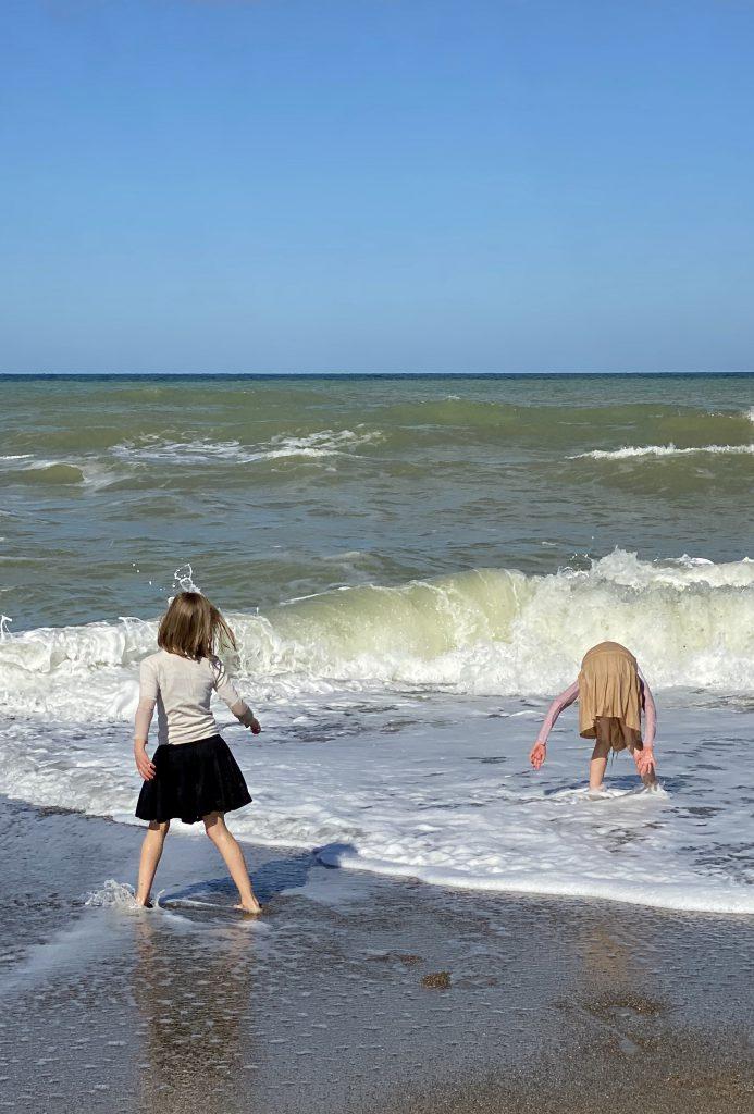 2 Kinder im Wellensaum, eins gebückt, das andere rennt